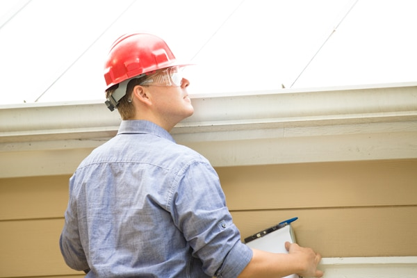 A roofing contractor doing roof inspection