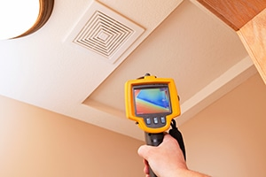 Infrared Thermal Imaging Camera Pointing to Attic Access for Inspection