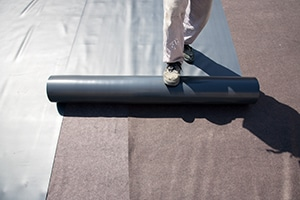 Roofer laying Roofing Membrane down on Flat Roof